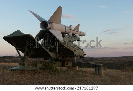 Missile on a rocket launcher viewed close up low angle at dusk as it points out over open countryside in a defensive position armed against threats - stock photo