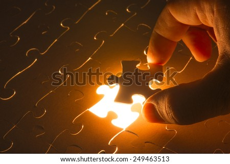 Missing jigsaw puzzle piece with light glow, business concept for completing the final puzzle piece - stock photo