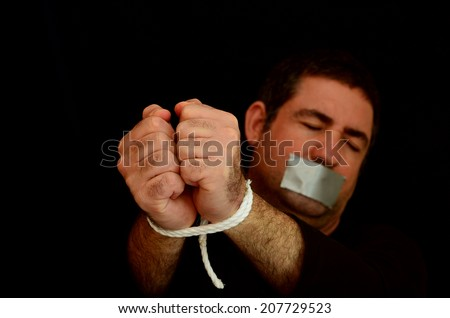 Missing kidnapped, abused, hostage, victim man with hands tied up with rope in emotional stress and pain, afraid, restricted, trapped, call for help, struggle, terrified, locked in a cage cell. - stock photo