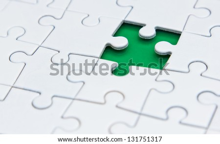 missing one piece of the puzzle on a green background - stock photo