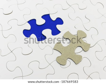 Missing piece of white puzzle and reveal blue color. - stock photo