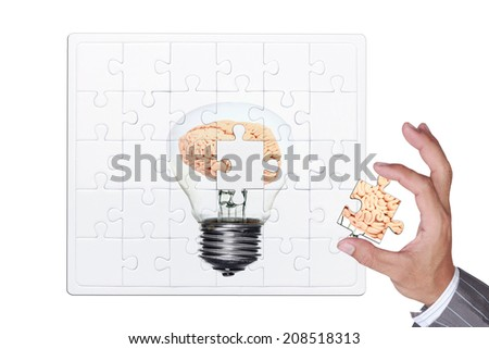 missing puzzle brain inside a light bulb jigsaw part in business hand for assembling complete concept for creativity isolate on white background with clipping path  - stock photo