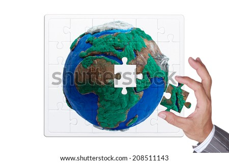 missing puzzle globe jigsaw part in business hand for assembling complete nation isolate on white background with clipping path - stock photo