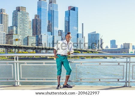 Missing You. Wearing white shirt,  green pants, leather shoes, a young black guy with mohawk hair is standing in the front of buildings, holding a white rose, thinking. Urban Casual Fashion - stock photo
