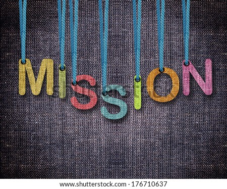 mission Letters hanging strings with blue sackcloth background. - stock photo