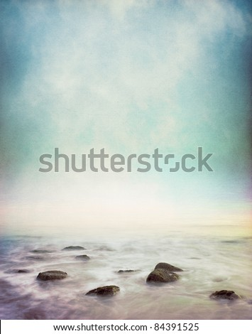 Mist and fog rising from a rocky ocean shore.  This image has a vintage paper texture and displays a pleasing grain pattern at 100%. - stock photo