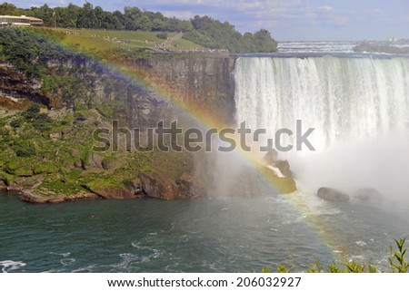 Mist and Rainbow over Niagara Falls, Canadian-American border - stock photo