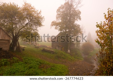 Mist at dawn in the village near the mountains - stock photo