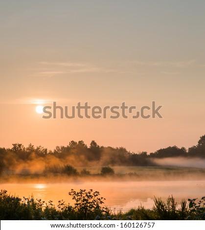 Mist drifts across the landscape illuminated by the rising sun. - stock photo
