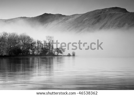 Mist hangs over the lake surface but the mountains raise clearly above it - stock photo