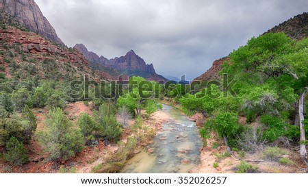 Mist shrouds peaks behind Eagle Crags after a storm sweeps across Watchman Peak and the Virgin River, at Zion National Park, near Springdale, Utah. - stock photo