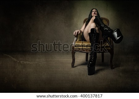mistress sitting in abstract room, dark background - stock photo