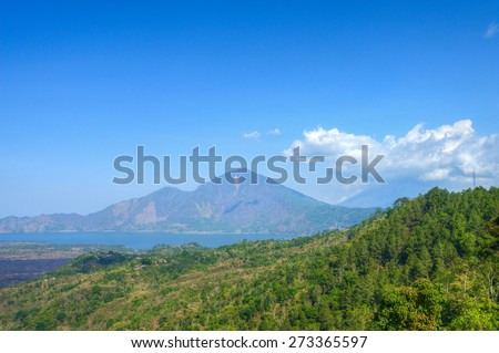 Misty Abang mountain and Agung volcano mountain at the back covered by cloud from Kintamani, Bali, Indonesia - stock photo