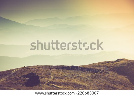 Misty autumn mountain hills landscape. A lone traveler walking along the trail.Filtered image:cross processed vintage effect. - stock photo