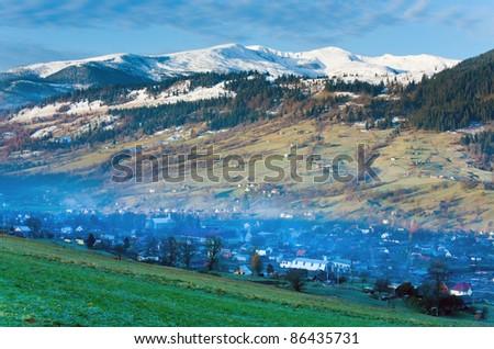 Misty early daybreak in autumn Carpathian mountain, Ukraine (Jasynja Village and Svydovets Range in far) - stock photo