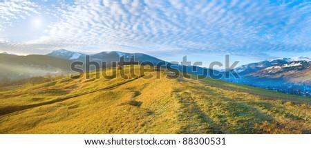 Misty early daybreak in autumn Carpathian mountain, Ukraine (Jasynja Village and Svydovets Range in far). Two shots stitch image. - stock photo