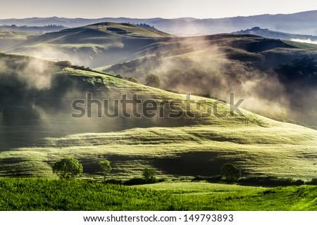 Misty hills in Tuscany at sunrise - stock photo
