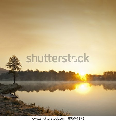 Misty lake in early winter morning - stock photo