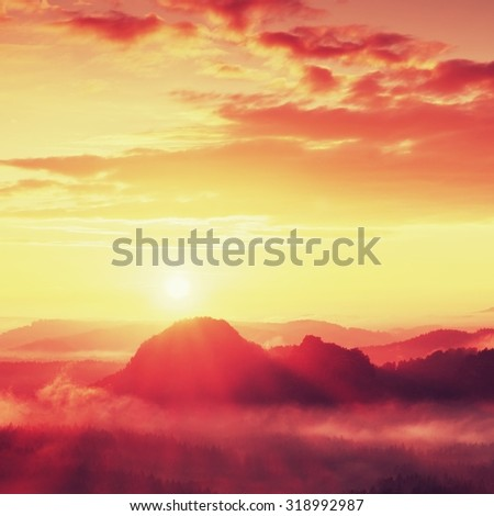 Misty landscape with fog between hills and orange sky within early sunrise - stock photo