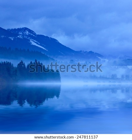 Misty landscape with lake in mountains - stock photo
