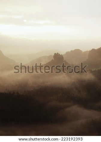 Misty melancholic morning. View into long deep valley full of autumn colorful mist. Fall landscape within daybreak after rainy night - stock photo