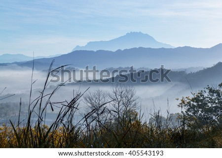 Misty morning with a mountain as background , Mount Kinabalu view at sunrise in Sepanggar Sabah, East Malaysia, Borneo - stock photo