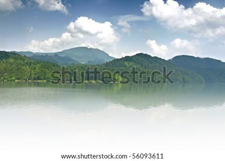 Misty mountain lake with blue sky - stock photo