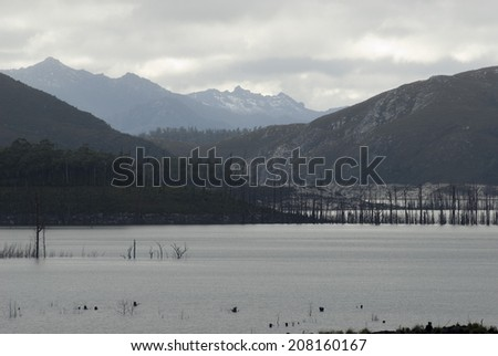 Misty overcast view of the scenic Lake Gordon in Tasmania, Australia created by damming the upper reaches of the Gordon River surrounded by mountain ranges - stock photo