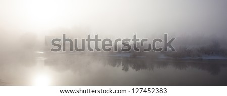 Misty River Scene with House in the Background - stock photo
