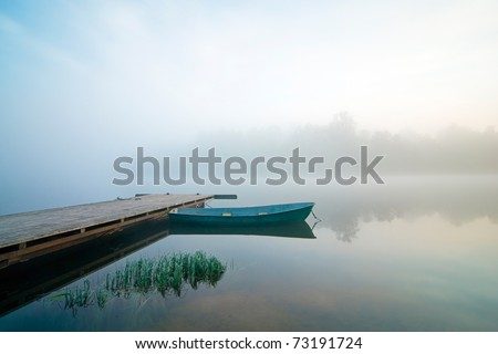 misty summer morning wit pier and boat - stock photo