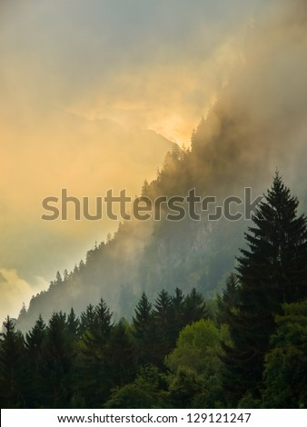 Misty Sunrise over Cloudy Mountains in the European Alps in France near Les Deux Alpes - stock photo