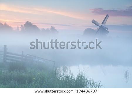 misty sunrise over Dutch windmill on farmland, Netherlands - stock photo