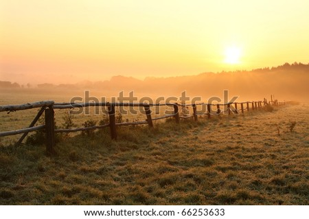 Misty sunrise over grassland with idyllic fence in the foreground. - stock photo