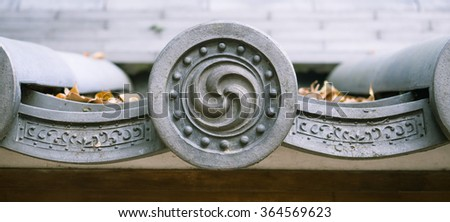 Mitsudomoe symbol on Shinto Buddhist shrine roof tile in Japan - stock photo