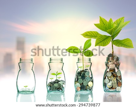 Mix coins and seed in clear bottle on cityscape photo blurred cityscape background,Business investment growth concept - stock photo