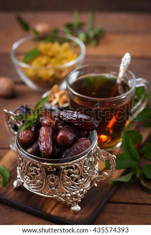 Mix dried fruits (date palm fruits, prunes, dried apricots, raisins) and nuts, and traditional Arabic tea. Ramadan (Ramazan) food. - stock photo