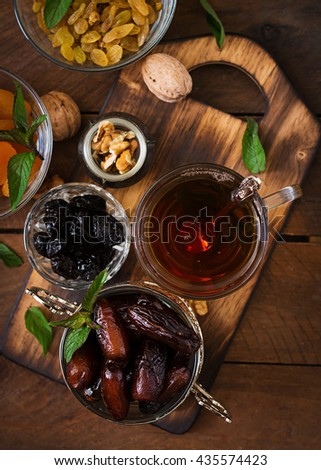 Mix dried fruits (date palm fruits, prunes, dried apricots, raisins) and nuts, and traditional Arabic tea. Ramadan (Ramazan) food. Top view - stock photo