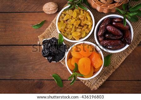 Mix dried fruits (date palm fruits, prunes, dried apricots, raisins) and nuts. Ramadan (Ramazan) food. Top view - stock photo
