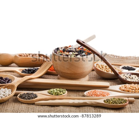 Mix from different beans, legumes, peas, lentils in spoon on the sackcloth on white - stock photo