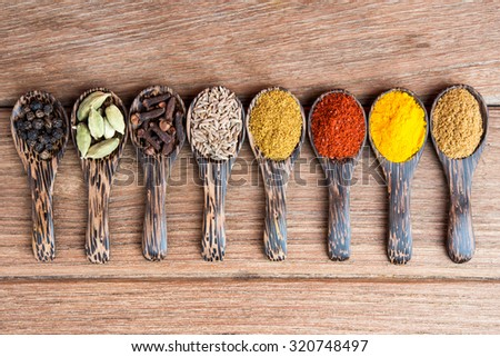 mix indian herbs on the spoon on the wooden table - stock photo