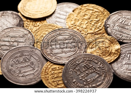 Mix of ancient golden and silver islamic coins, closeup, selective focus - stock photo