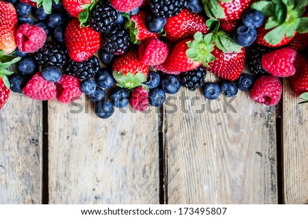 Mix of berries on rustic wooden background - stock photo