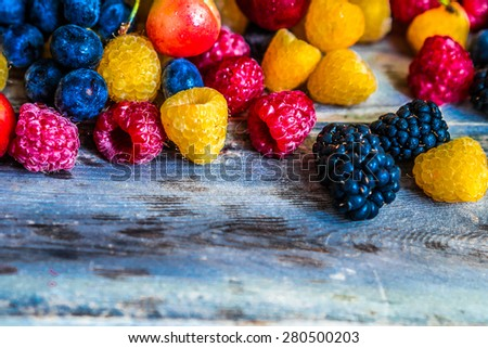 Mix of berries on wooden background - stock photo