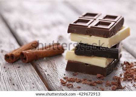 Mix of chocolate with cinnamon sticks on wooden table - stock photo