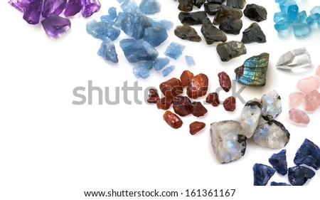 Mix of colorful unpolished gemstones on the white background. Beautiful gems background. - stock photo