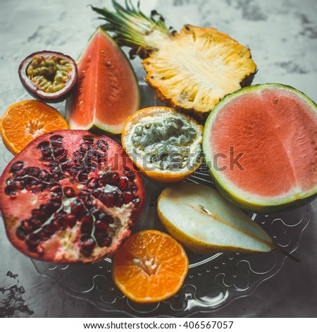 Mix of different tropical fruits on a glass dish - stock photo