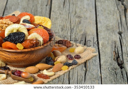 Mix of dried fruits and nuts in a wooden bowl - symbols of judaic holiday Tu Bishvat. Copyspace background - stock photo