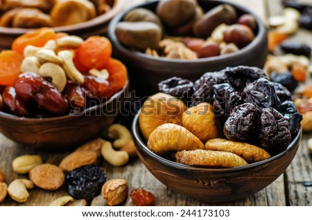 mix of dried fruits and nuts on a dark wood background. tinting. selective focus - stock photo