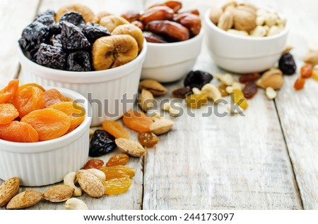 mix of dried fruits and nuts on a white wood background. tinting. selective focus - stock photo