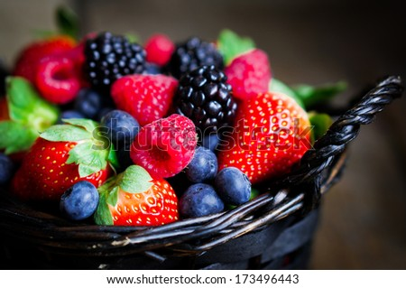 Mix of fresh berries in a basket on rustic wooden background - stock photo